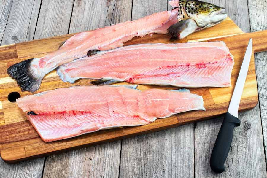 Trout fillets on cutting board with filleting knife